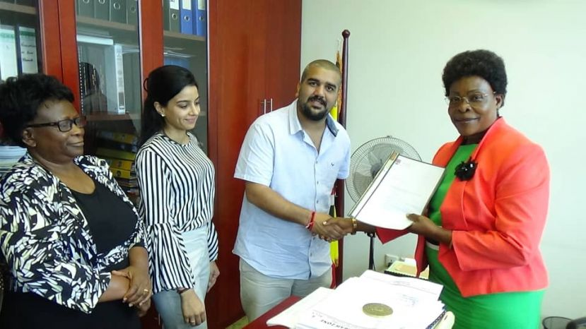 Minister Betty Kamya receiving paperwork from Rajiv Ruparelia