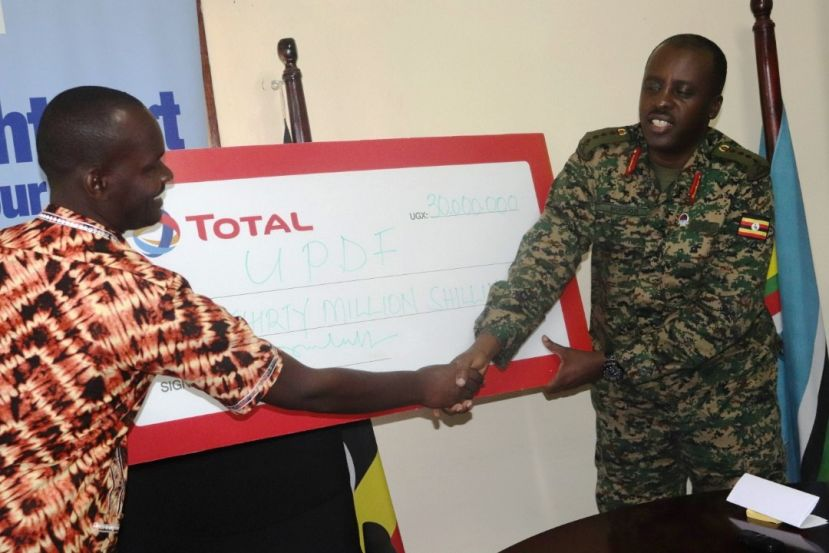 CDF General David Muhoozi hands over UGX30m cheque donated by Total Uganda to headmaster of NAmagera CU PS