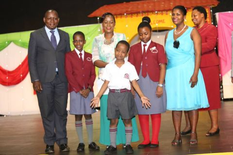 The minister (3rd R) poses for a photo with the head boy, heady girl and Fresh Kid at Kampala Parents School